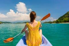 Junge Frau, die ein Kanu während der Ferien in Flores-Insel, Indonesien schaufelt Lizenzfreies Stockbild