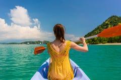 Junge Frau, die ein Kanu während der Ferien in Flores-Insel, Indonesien schaufelt Stockbilder