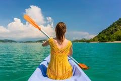 Junge Frau, die ein Kanu während der Ferien in Flores-Insel schaufelt Stockfotografie