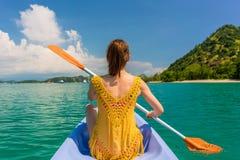 Junge Frau, die ein Kanu während der Ferien in Flores-Insel schaufelt Lizenzfreie Stockbilder