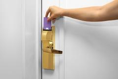 Junge Frau, die ein keycard vor dem elektronischen Sensor einer Zimmertür hält lizenzfreie stockfotografie