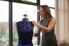 Junge Frau, die ein Kleid auf einem Mannequin, Damenschneiderin im Arbeitsraum versucht lizenzfreies stockbild