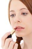 Junge Frau, die ein Lippenstift setzt Lizenzfreies Stockbild