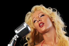 Junge Frau, die in ein Mikrofon singt Stockbilder