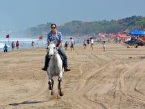 Junge Frau, die ein Pferd auf Legian-Strand reitet lizenzfreies stockbild