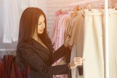 Junge Frau, die ein Preisschild auf ein Mall oder ein Bekleidungsgeschäft betrachtet Lizenzfreie Stockfotos