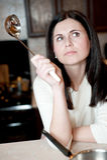 Junge Frau, die an ein Rezept denkt Lizenzfreie Stockfotografie