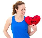 Junge Frau, die ein rotes Herz hält lizenzfreie stockbilder