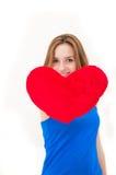 Junge Frau, die ein rotes Herz hält lizenzfreies stockfoto