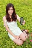 Junge Frau, die ein Selbstporträt durch die Anwendung des Handys nimmt Lizenzfreie Stockfotografie