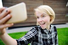 Junge Frau, die ein Selbstporträt mit intelligentem Telefon nimmt Lizenzfreie Stockfotografie