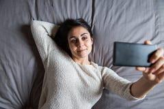 Junge Frau, die ein selfie auf Bett nimmt Lizenzfreies Stockfoto