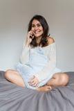 Junge Frau, die ein selfie auf Bett nimmt Stockfotografie