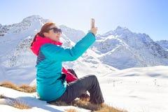 Junge Frau, die ein selfie an ihrem Telefon auf eine schöne Gebirgsoberseite nimmt Blume im Schnee Lizenzfreie Stockfotos