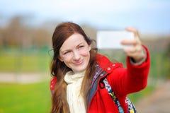 Junge Frau, die ein selfie mit intelligentem Telefon nimmt Stockfotos