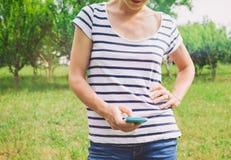 Junge Frau, die ein smartphone verwendet Stockfotos