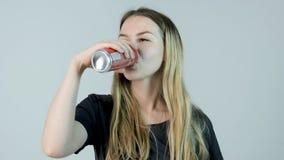 Junge Frau, die ein Soda trinkt Trinkendes Soda und Lächeln der jungen Schönheit lizenzfreies stockfoto