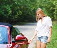 Junge Frau, die ein Sportauto öffnet Lizenzfreies Stockbild