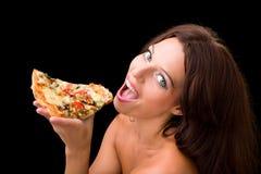 Junge Frau, die ein Stück Pizza isst Stockfotos