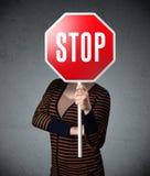 Junge Frau, die ein Stoppschild hält Lizenzfreies Stockbild