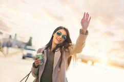 Junge Frau, die ein Taxi auf der Straße in der Stadt hagelt Stockbilder