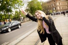 Junge Frau, die ein Taxi auf der Straße in der Stadt hagelt Lizenzfreies Stockfoto