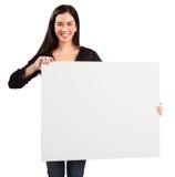 Junge Frau, die ein unbelegtes weißes Zeichen anhält Stockfotos
