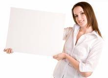 Junge Frau, die ein unbelegtes weißes Zeichen anhält Stockbild