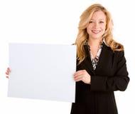 Junge Frau, die ein unbelegtes weißes Zeichen anhält Stockfoto