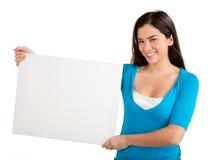Junge Frau, die ein unbelegtes weißes Zeichen anhält Stockfotografie