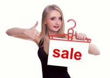 Junge Frau, die ein Verkaufszeichen anhält Lizenzfreie Stockfotos