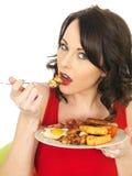 Junge Frau, die ein volles englisches Frühstück isst lizenzfreie stockfotos