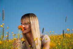 Junge Frau, die eine Blume in der Wiese riecht Lizenzfreie Stockfotografie