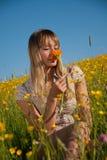 Junge Frau, die eine Blume in der Wiese riecht Stockfotografie