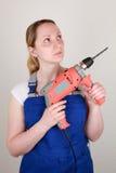 Junge Frau, die eine Bohrmaschine in ihren Händen hält lizenzfreies stockfoto