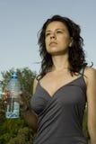 Junge Frau, die eine Flasche Wasser anhält Lizenzfreies Stockfoto