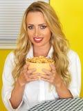 Junge Frau, die eine gelbe Schüssel Frühstückskost aus Getreide hält Lizenzfreie Stockfotografie