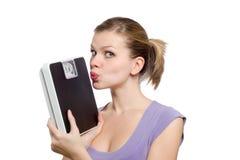Junge Frau, die eine Gewichtskala küßt Lizenzfreie Stockfotos