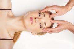 Junge Frau, die eine Hauptmassage auf Weiß empfängt stockbild