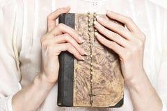 Junge Frau, die eine heilige Bibel und ein Rosenbeet hält Stockbild