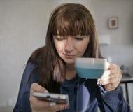 Junge Frau, die eine Kaffeetasse hält und das Telefon verwendet lizenzfreie stockbilder