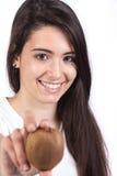 Junge Frau, die eine Kiwi anhält Lizenzfreies Stockbild