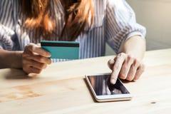 Junge Frau, die eine Kreditkarte hält und Smartphone verwendet stockfotografie