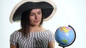 Junge Frau, die eine Kugel, entscheiden spinnt, wohin man auf Ferien geht stock footage