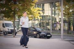 Junge Frau, die eine Laufkatze hinunter die Straße zieht Stockfoto
