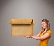 Junge Frau, die eine leere Pappschachtel hält Lizenzfreies Stockbild