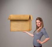 Junge Frau, die eine leere Pappschachtel hält Stockbilder