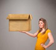 Junge Frau, die eine leere Pappschachtel hält Lizenzfreie Stockfotografie