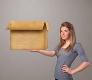Junge Frau, die eine leere Pappschachtel hält Stockfotografie