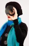 Junge Frau, die eine Linse im hijab und im bunten Schal hält Stockbilder